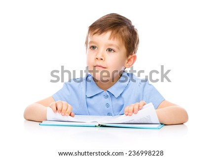 Cute little child play with book while sitting at table, isolated over white - stock photo