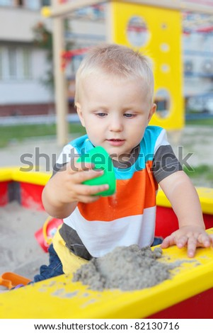 cute little child playing in the sandbox on the playground - stock photo