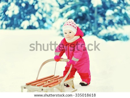 Cute little child playing with sled in winter forest - stock photo