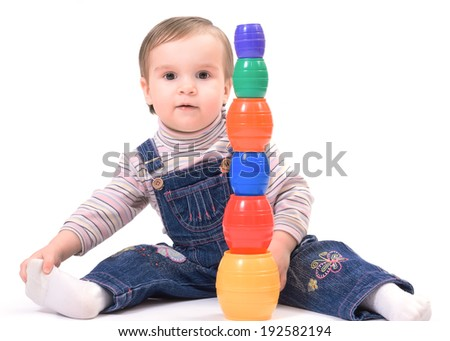Cute little child playing with toys while sitting on floor on white background - stock photo