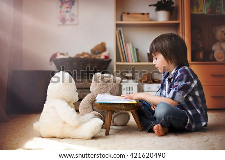Cute little child, preschool boy, reading a book to his teddy bears at home, sun rays coming through window, dust in the air - stock photo