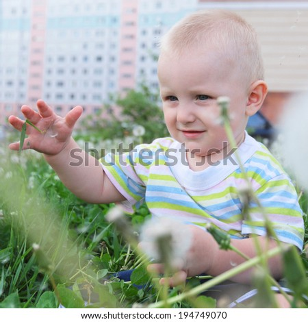 cute little child sitting in the grass in the city near the house - stock photo