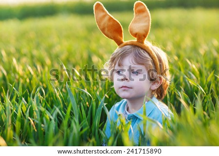 Cute little child with Easter bunny ears playing in green grass on sunny spring day, celebrating Easter holiday - stock photo