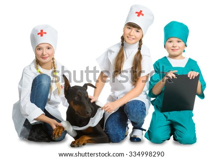Cute little children dressed like doctor treated dog or doberman  isolated on white background. Veterinary concept - stock photo