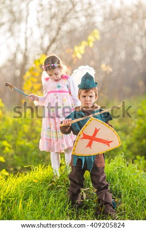 Cute little children dressed up as a knight and a fairy playing in the woods