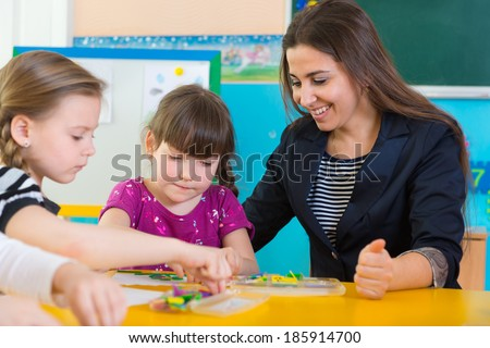 Cute little children having applique lesson at kindergarten - stock photo