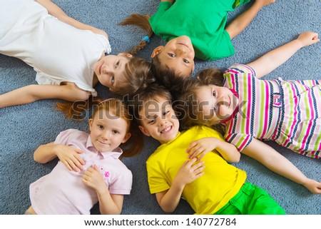 Cute little children lying on floor in kindergarten - stock photo