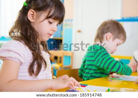 Cute little children on lesson at kindergarten - stock photo