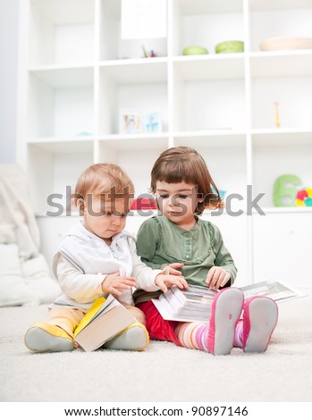 Cute little children reading on the floor at home - stock photo
