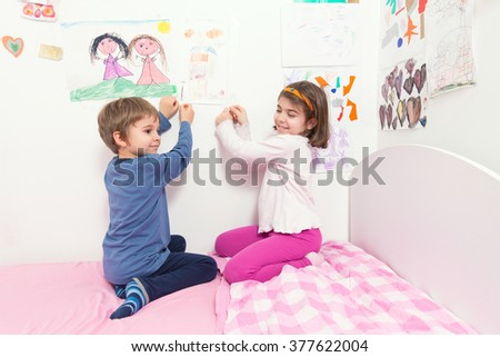 Cute little children setting their drawings on the wall of their room - stock photo