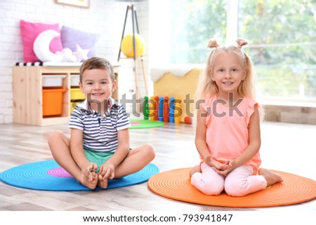 Cute little children sitting on floor at home