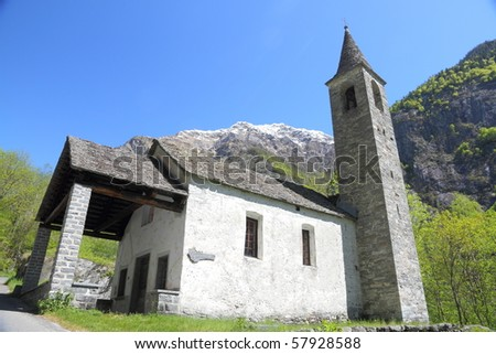 cute, little church built from stone standing amidst fresh spring green in a mountain valley in Ticino,Switzerland