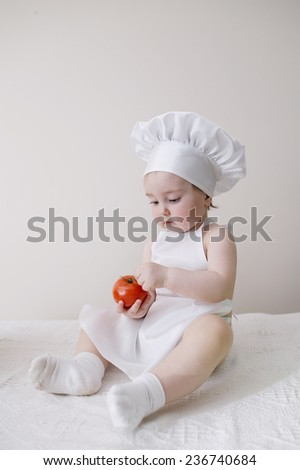 cute little cook eats tomato - stock photo