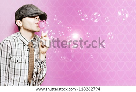 Cute Little Cupid Boy Sending Love Bubble Kisses Through Heart Shape Blower On Valentines Day - stock photo