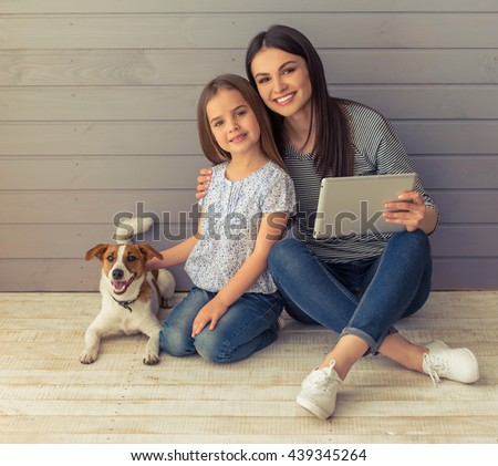 Cute little daughter and her beautiful young mother are looking at camera and smiling while posing with their dog. Mom is using a tablet - stock photo