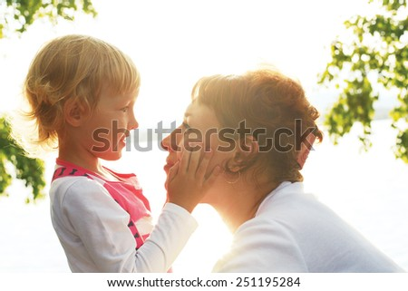 cute little daughter gently stroking her mother's face. mother and daughter looking at each other's eyes - stock photo