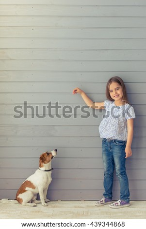 Cute little daughter is smiling and looking at camera while playing with her dog - stock photo