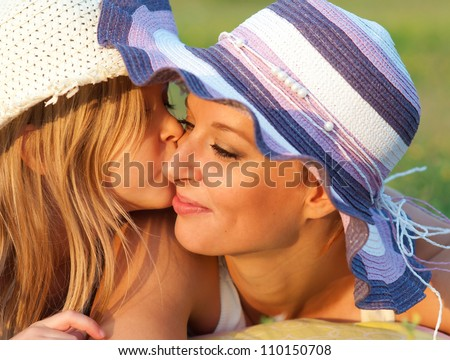Cute little daughter kissing her mother in the cheek on sunny summer day. - stock photo