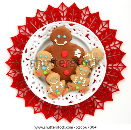 Cute little decorated gingerbread men on white plate and red felt mat in square format from overhead