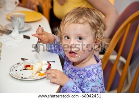 Cute little European toddler girl enjoying a piece of birthday cake. - stock photo