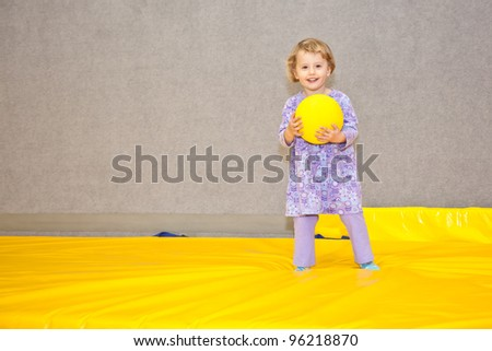 Cute little European toddler girl having fun at indoor playground. - stock photo