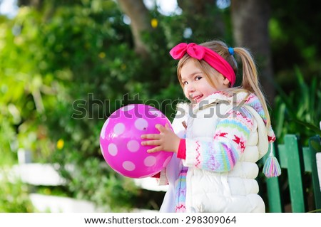 Cute little fashion girl playing with ball in kitten clothes outdoor - stock photo