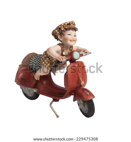 Cute little figurine of a happy playing kid riding a red retro scooter, isolated on white background. - stock photo