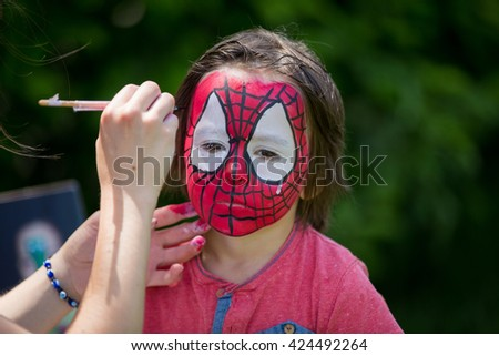 Cute little five years old boy,. having his face painted as spider on his birthday party - stock photo