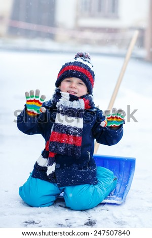 Cute little funny boy in colorful winter clothes having fun with snow shovel, outdoors during snowfall. Active outdoors leisure with children in winter. Kid with warm hat, hand gloves and scarf  - stock photo