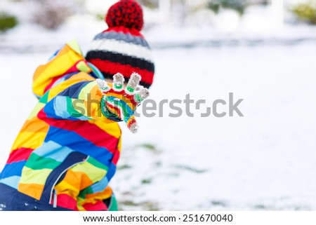 Cute little funny boy in colorful winter clothes playing fighting with snow ball, outdoors  on cold day. Active outoors leisure with children in winter. Selective focus on hand in glove - stock photo
