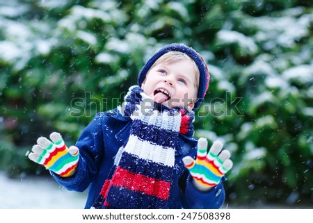 Cute little funny child in colorful winter clothes having fun with snow, outdoors during snowfall. Active outdoors leisure with children in winter. Kid with warm hat, hand gloves and scarf  - stock photo