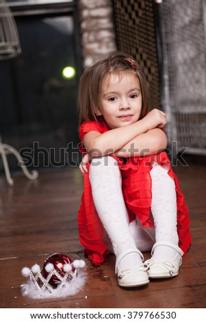 Cute little girl about four years old in a red dress sitting on the floor - stock photo