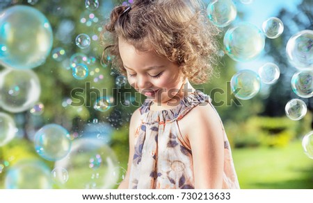 Cute, little girl among hundreds of flying soap bubbles