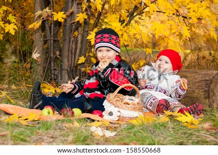 Cute little girl and boy eating bagels in autumn park