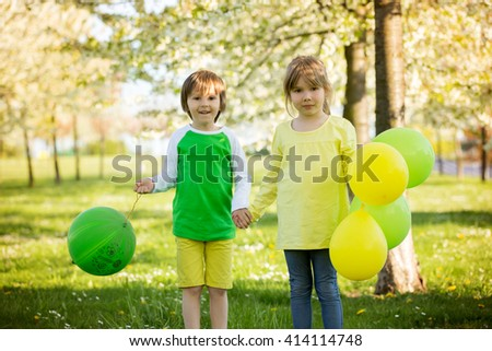 Cute little girl and boy, friends, playing with balloons in a blooming apple tree garden, spring sunny late afternoon