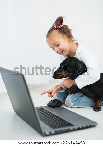 Cute Little Girl  And Dachshund Use Laptop - stock photo