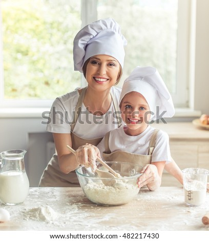 Cute little girl and her beautiful mom in aprons and cooking hats are looking at camera and smiling while kneading the dough in the kitchen