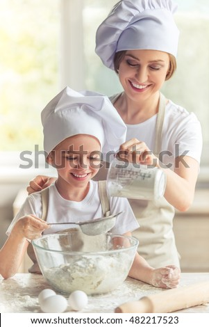 Cute little girl and her beautiful mom in aprons and cooking hats are smiling while preparing the dough for baking in the kitchen