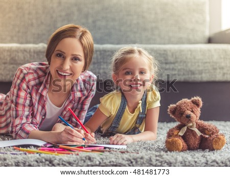 Cute little girl and her beautiful mother are drawing, looking at camera and smiling while lying on the floor at home