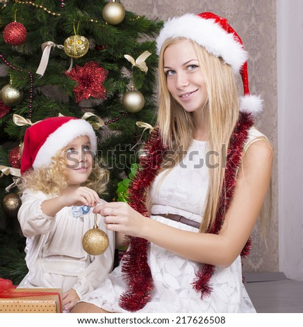 cute little girl and her beautiful mother in santa's hat posing beside a decorated Christmas tree - stock photo