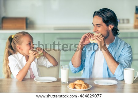 Cute little girl and her handsome father are eating sandwiches for breakfast and looking at each other, sitting in kitchen at home