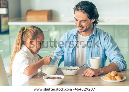 Cute little girl and her handsome father are smiling while having breakfast in kitchen at home. Girl is pouring milk into dad's cereals