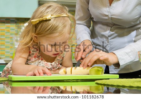 Cute little girl and her mother cutting banana with kiwi in kitchen - stock photo
