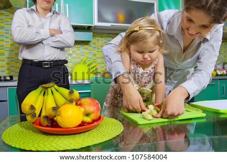 Cute little girl and her mother cutting banana with kiwi in kitchen