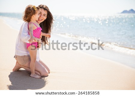 Cute little girl and her mother enjoying a sunny day at the beach together - stock photo