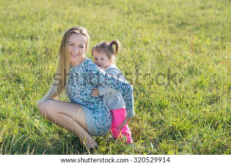 Cute little girl and her mother playing in the park
