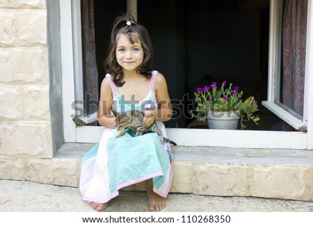 Cute little girl  and kitten to play out window - stock photo