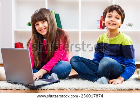 Cute little girl and little boy are using laptop.Children using laptop - stock photo