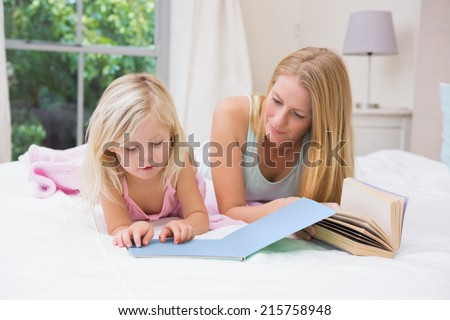 Cute little girl and mother on bed reading at home in the bedroom - stock photo