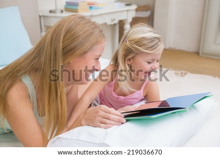 Cute little girl and mother on bed reading at home in the bedroom